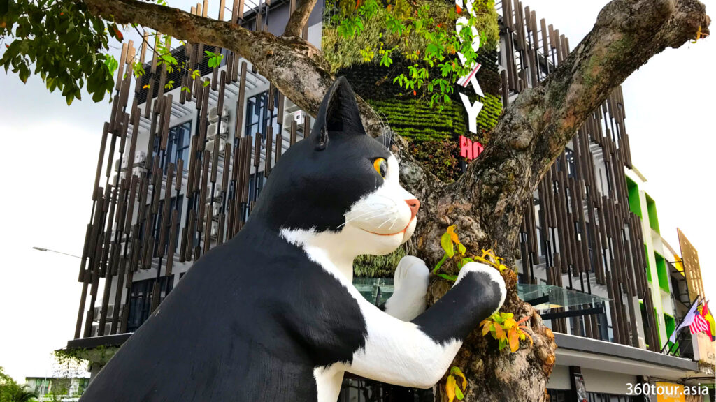 The lovely black and white cat statue leaning on the tree.